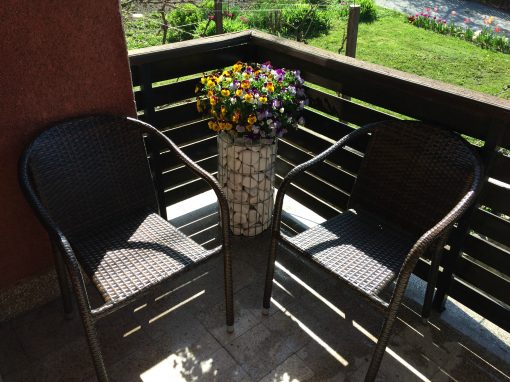 Gabion pillar with flowers on the balcony with chairs